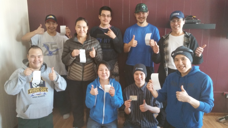 A group of Indigenous youth doing thumbs up and proudly showing credentials earned