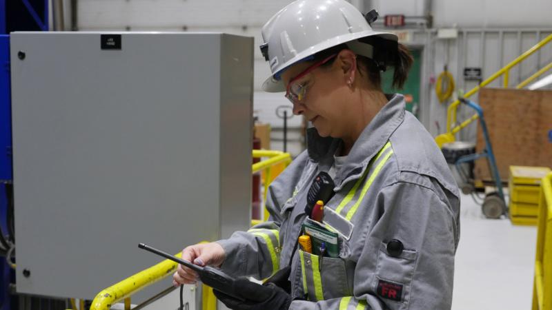 Aboriginal woman electrician examining a hand held radio