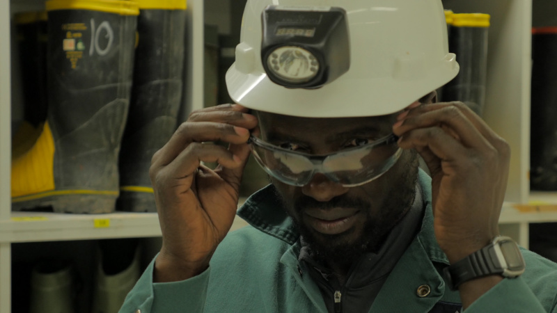 A close up of a visible minority male putting on safety glasses