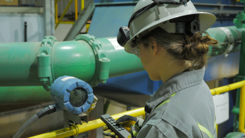 A female technician operating equipment in a plant