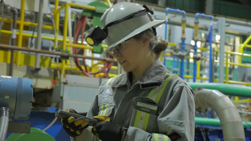 Technicienne utilisant de l'équipement dans une usine