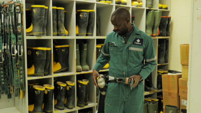 A visible minority male putting on a safety belt in a room that contains storage of personal protective equipment. Safety boots and belts are in the background.
