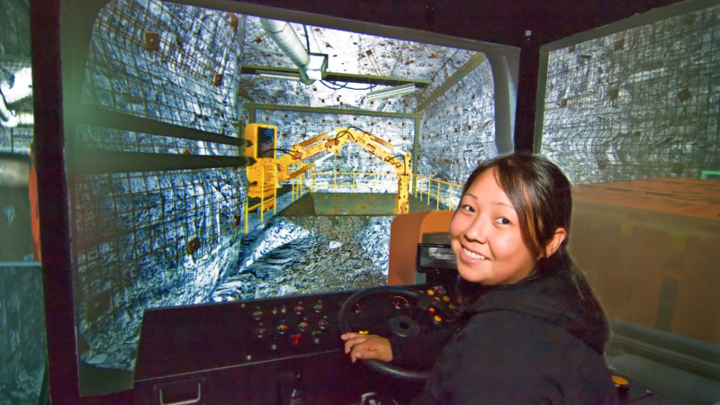 An Aboriginal woman controlling an equipment simulator. A screen shows how the equipment is being controlled.